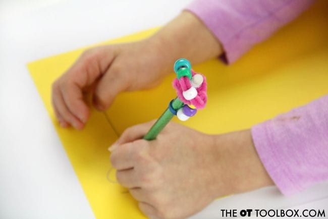 Child writing with a pencil that has a fidget topper made from pipe cleaners and beads