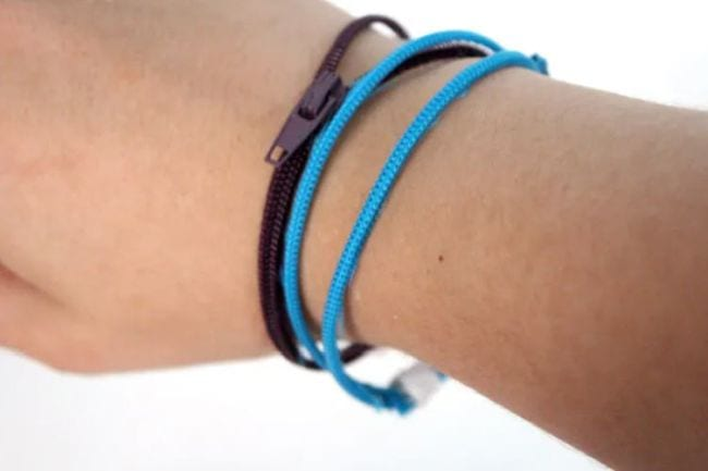 Student wearing blue and black bracelets made of zippers