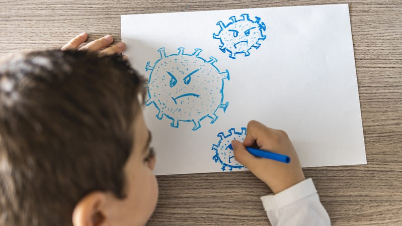 Young student drawing a germ in blue
