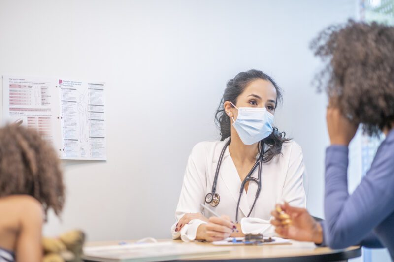 Woman doctor talking to patient - science career