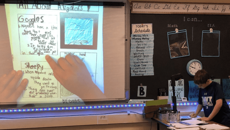 student uses a document camera to show work to the class