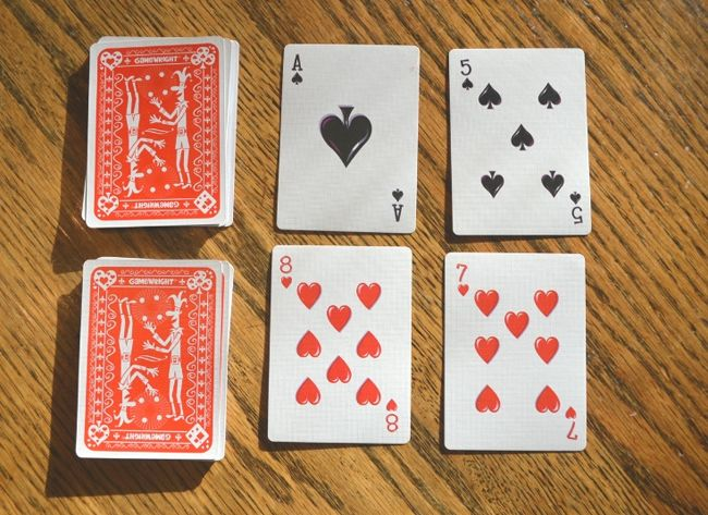 Two decks of playing cards with four cards face up next to them