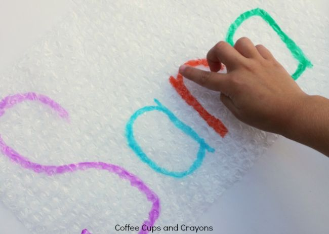 Student popping bubbles on bubble wrap while tracing the letters of the name Sara (Dollar Store Hacks)