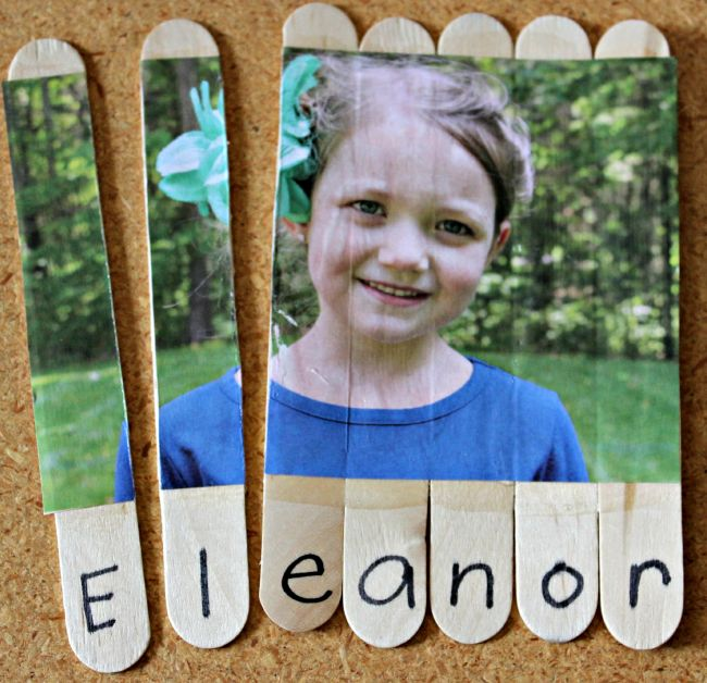 Child's picture glued to a series of wood craft sticks and cut apart, with the letters of her name underneath (Dollar Store Hacks)