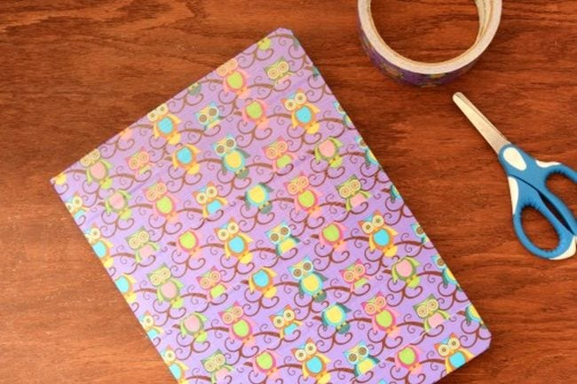 Composition book covered in owl-printed duct tape, with tape roll and scissors
