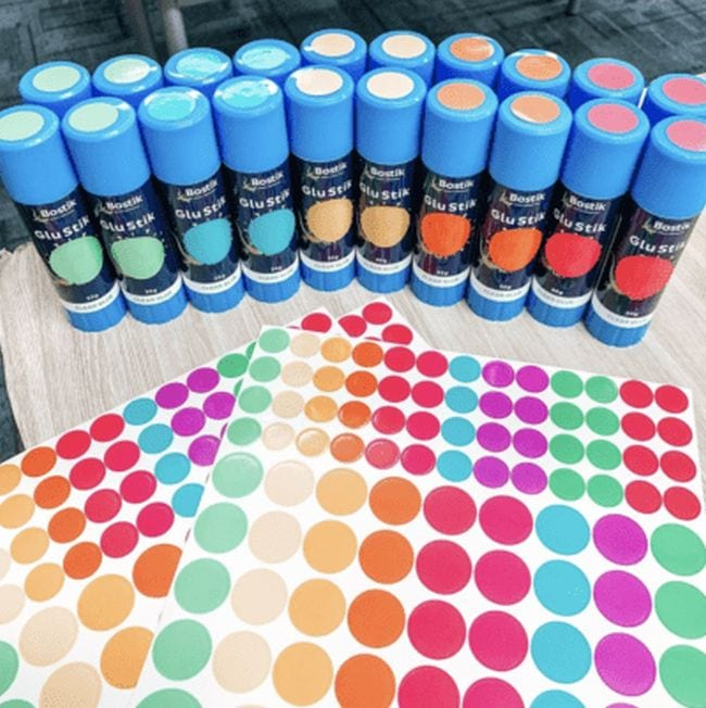 Glue sticks with colored dot stickers on the lids and bodies