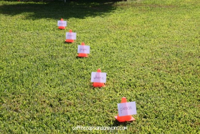 Series of small orange cones with words taped to them laid out on grass