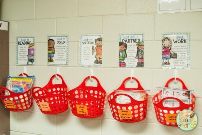 Red plastic tote baskets hung on plastic hooks on a wall (Dollar Store Hacks)