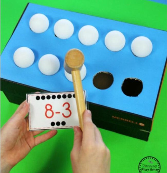 Student using a wooden mallet to tap ping pong balls into a cardboard box while holding a card saying 8-3