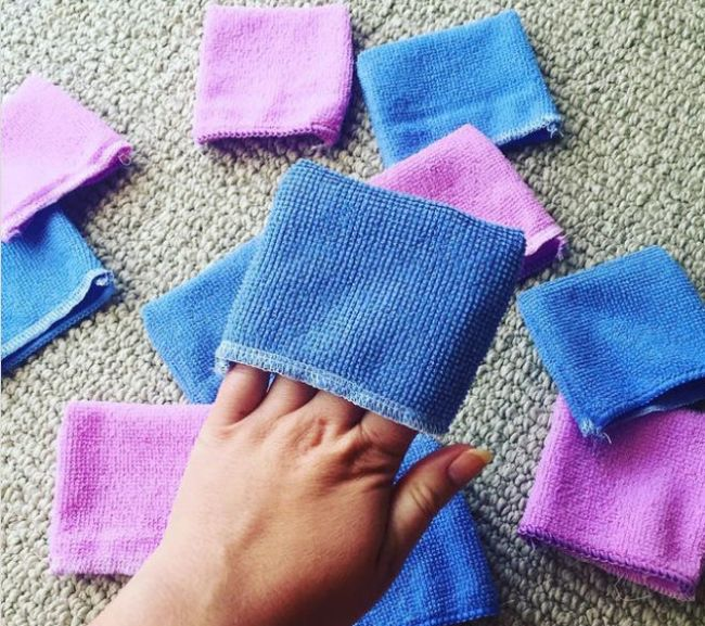 Teacher holding blue and pink eraser mitts made from microfiber cloth