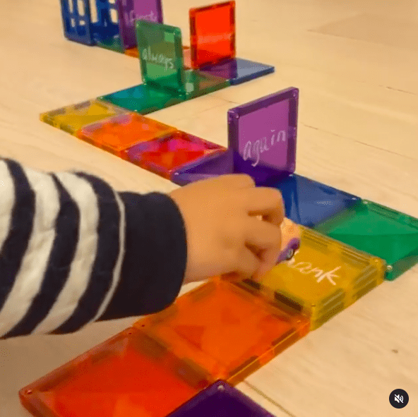 Child's hand driving a toy car over a path of magnetic tiles with sight words written on them
