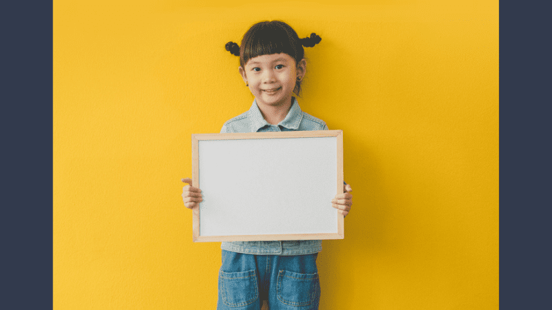 Young smiling girl standing in front of bright yellow wall holding a blank dry erase board