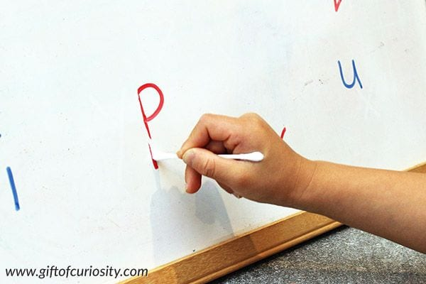 Student using a cotton swab to erase a letter drawn on a whiteboard
