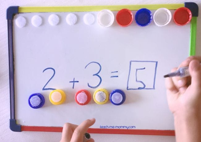 Student using dry erase board and bottlecaps to write 2 + 3 = 5