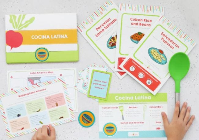 Child holding cooking tools and recipe cards from Raddish Kids (Educational Subscription Boxes)
