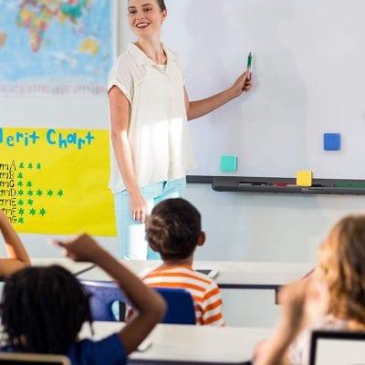 Woman teaching a class of students -- 1st grade classroom supplies