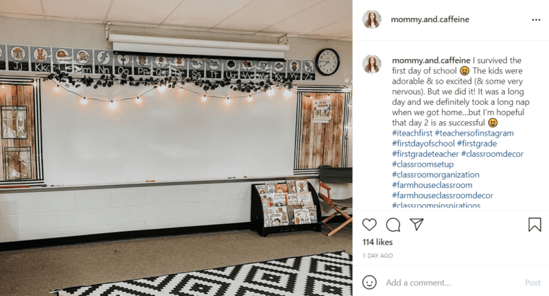 The whiteboard in a classroom with farmhouse classroom décor accents including a black and white rug, faux wood paneling, and string lights.
