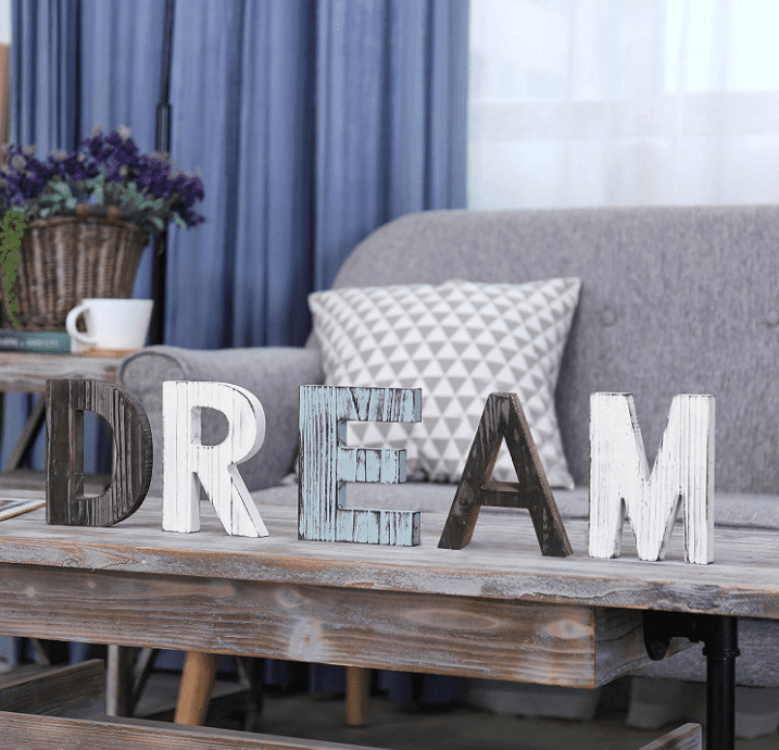 """Multicolored and multitextured letters spell the word """"DREAM"""" in all caps on a coffee table with a grey couch in the background."""
