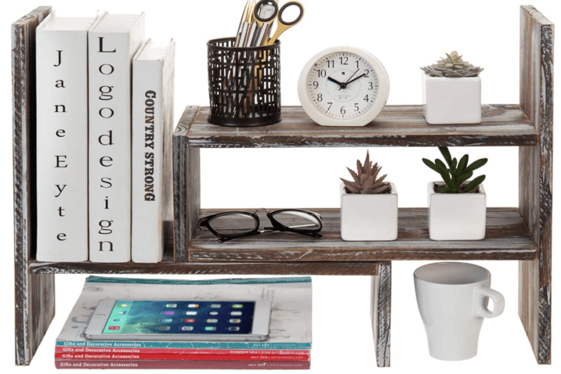 A rustic wooden organizational shelf with miscellaneous items on it such as books, succulents, a clock, and a mug used to exemplify the storage capabilities of the item.