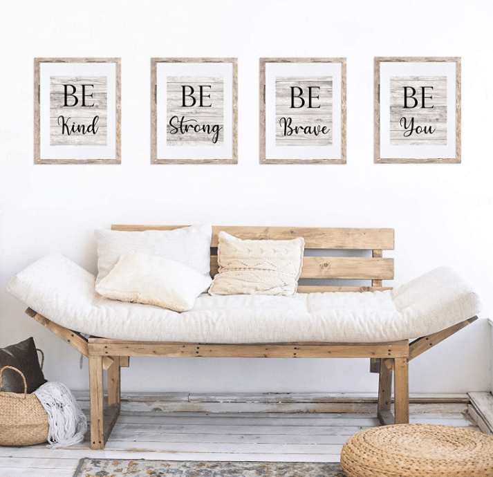 """Four picture frames with the sayings """"Be Kind,"""" """"Be Strong,"""" """"Be Brave,"""" and """"Be You"""" on a wall above a wooden bench with white cushions and pillows."""
