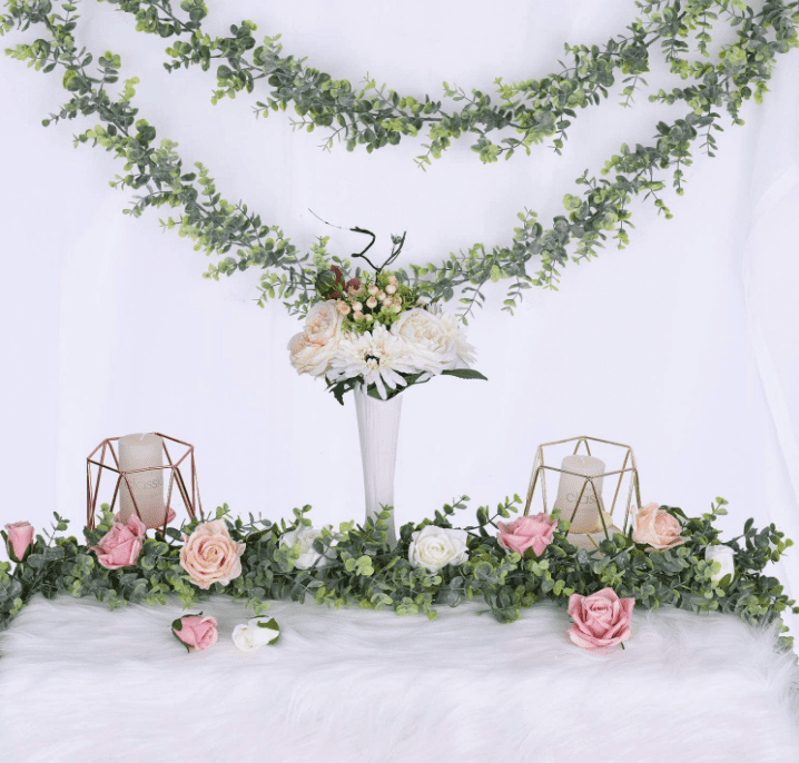 Floral garland hanging in a bunting style on a wall with a table featuring more garland, candles, and a bouquet of flowers in a vase below it.
