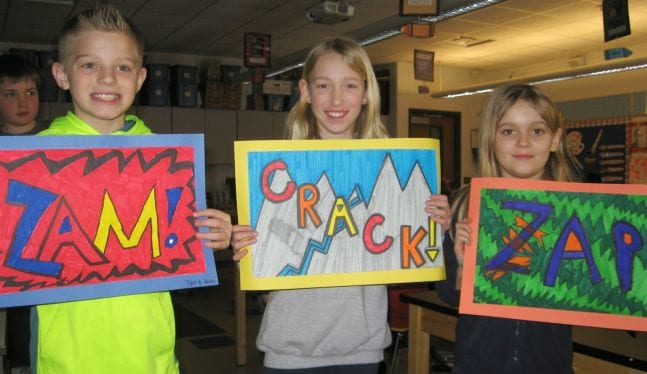 Fifth grade art students holding illustrations of the words Sam, Crack, and Zap