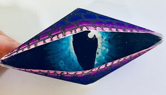 Purple paper eye folded out of paper and colored