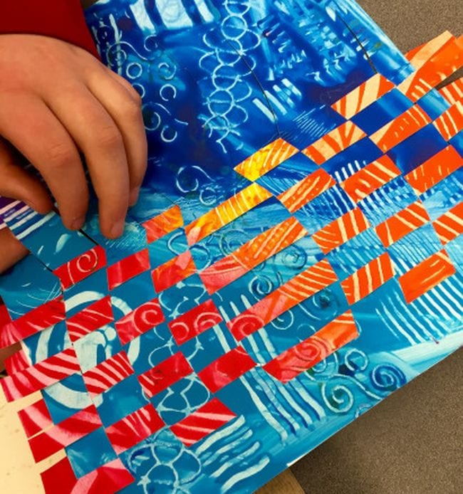 Student weaving together two pages painted in different patterns (Fifth Grade Art)