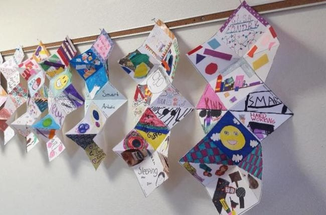 Folded paper squash books hung along the wall (Fifth Grade Art)