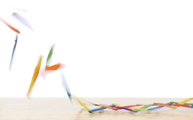 Colorful wood craft sticks flying into the air from a table