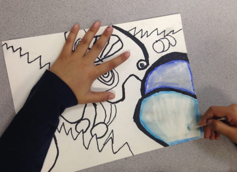 First grade art student adding blue watercolor to a page of scribbles using a cotton swab