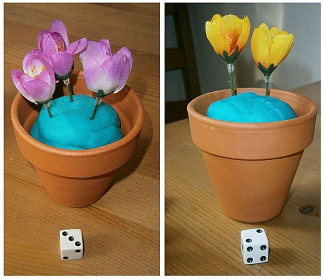 Flower pots with playdough soil, filled with artificial flowers matching the number shown on the dice nearby (First Grade Math Games)