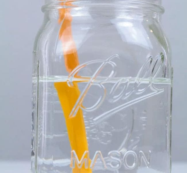 Mason jar of water with a pencil in it, viewed from the side