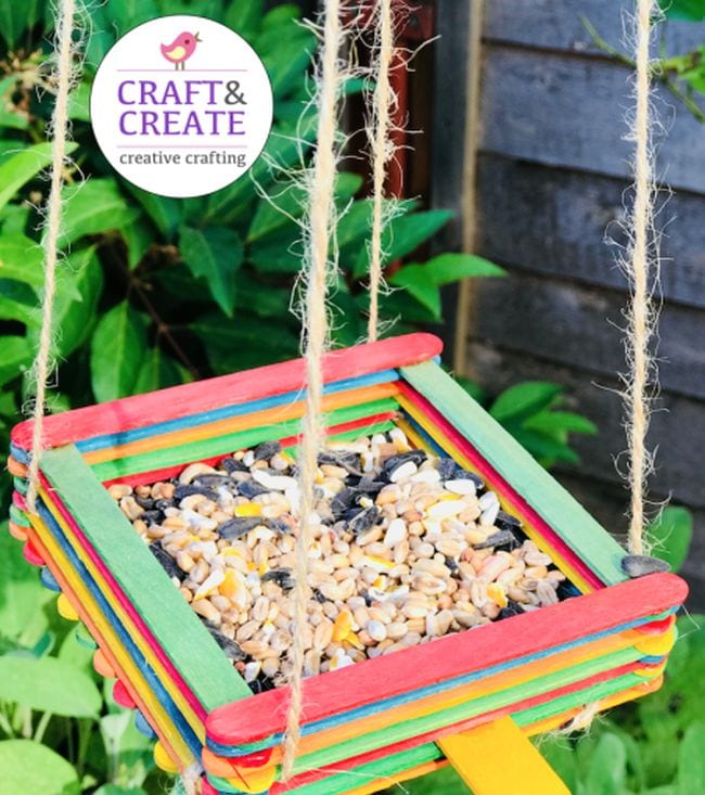 Platform-style bird feeder built from colorful wood craft sticks and filled with mixed seed (First Grade Science Experiments)