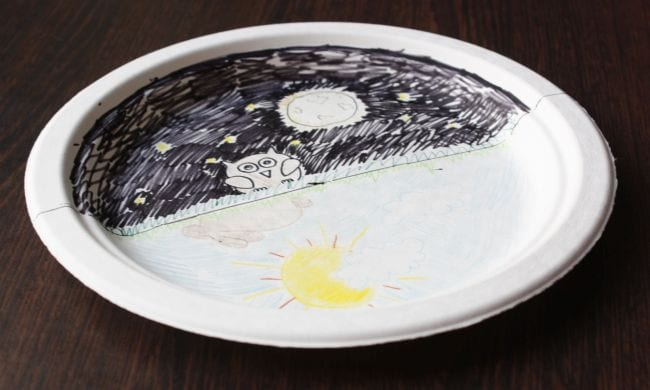 Paper plate divided in half, with one showing a night sky and owl, the other showing a blue sky and sun