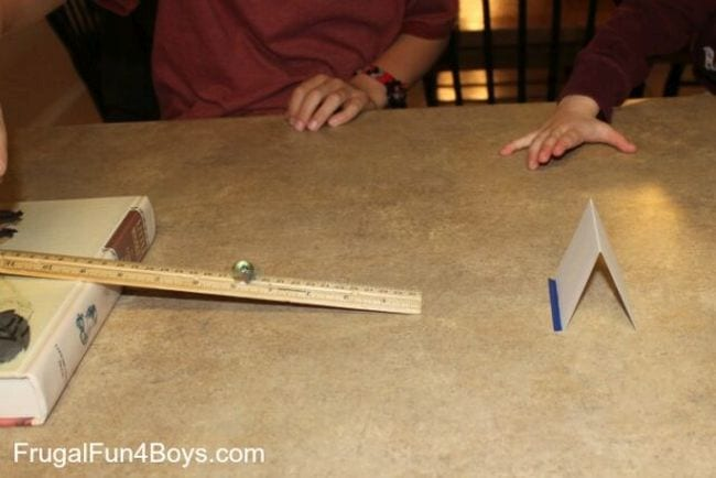 A ruler propped on one side on a flat book, with a marble rolling down it toward a folded index card (First Grade Science Experiments)