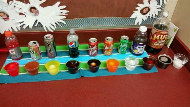 A series of plastic cups filled with varieties of soda, juice, and other liquids, with an egg in each