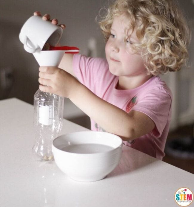 Young student pouring yeast through a funnel into a plastic bottle