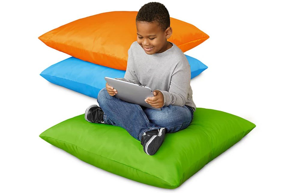 Student sitting on giant cushion with two others