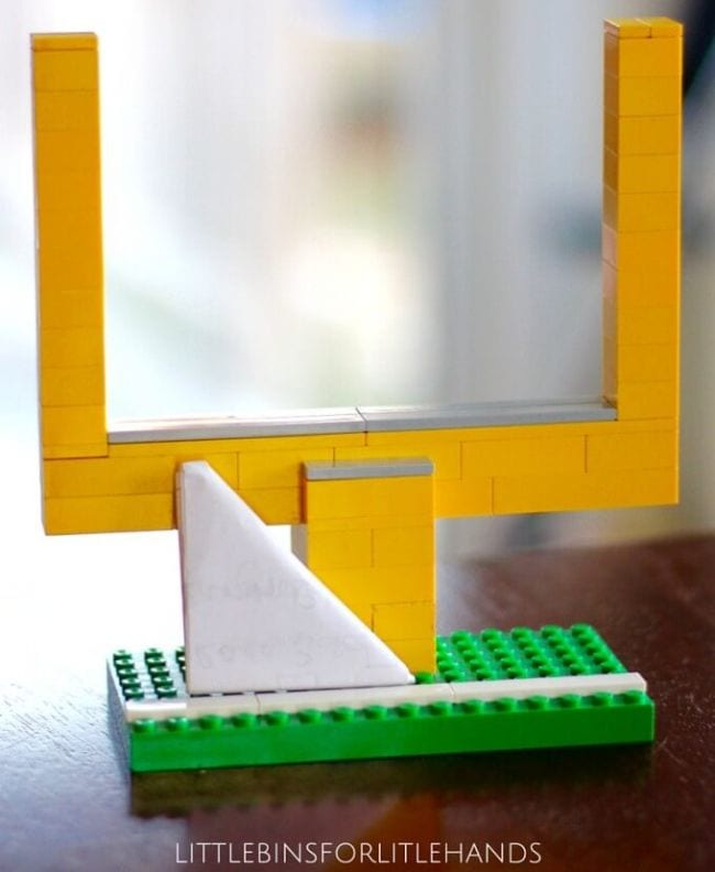 Yellow football goalposts built from LEGO bricks with a folded triangle paper football (Football Activities)