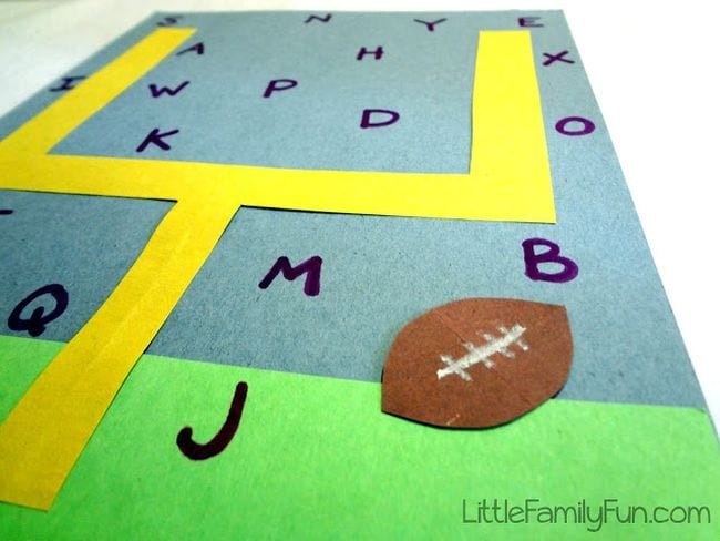 Yellow goal post surrounded by letters of the alphabet with a paper football (Football activities)