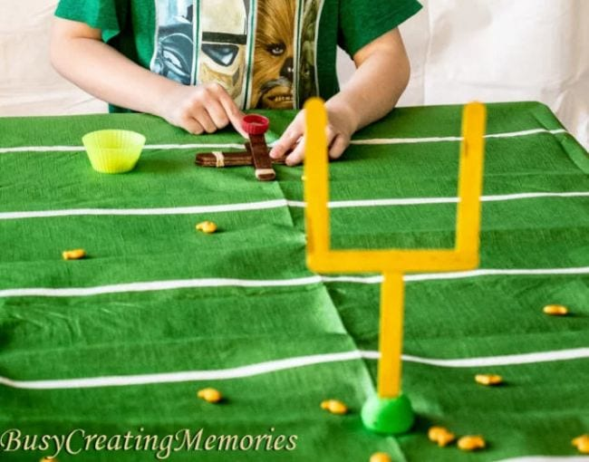 Child using a catapult made of wood craft sticks to launch goldfish crackers through miniature goal posts (Football Activities)