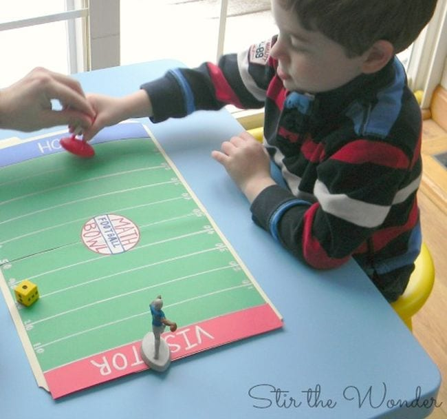 Child moving a plastic football player figurine down a paper football field (Football Activities)