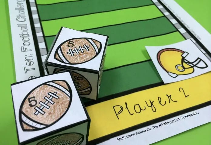 Paper dice printed with numbered footballs on a paper football field