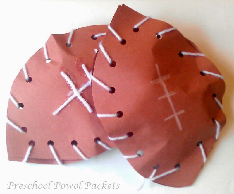 Paper footballs made by sewing two pieces of construction paper together with yarn