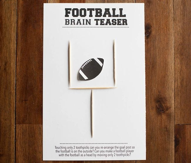Goalpost made from 4 toothpicks laid on top of a worksheet with a football printed on it