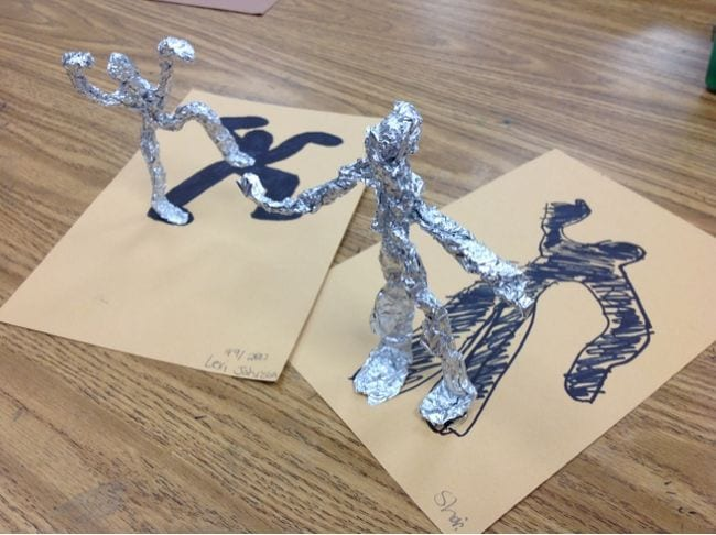 Two figures sculpted from aluminum foil, with their shadows drawn below