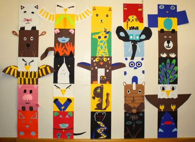 Colorful construction paper totem poles showing a variety of animals