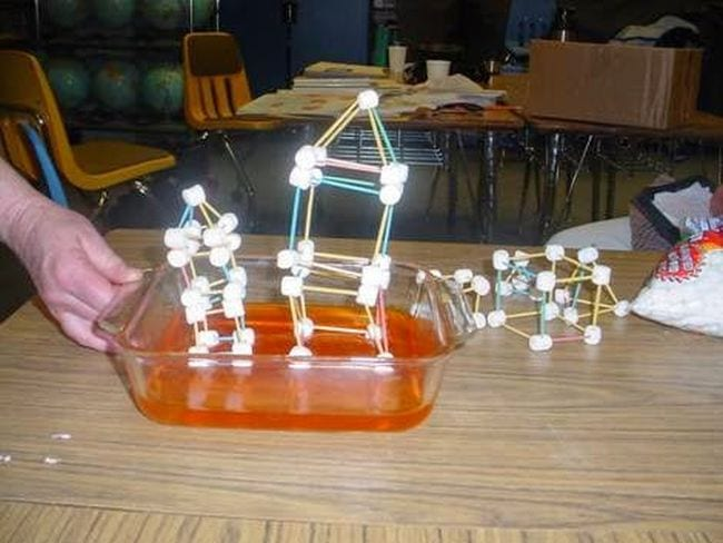 Fourth grade science teacher's hand shaking a pan of Jello topped with a house model made of toothpicks and marshmallows