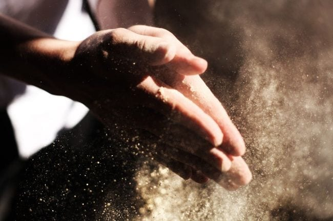 Student's hands covered in flour in a cloud of flour dust